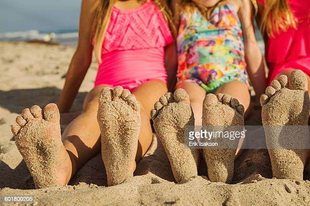 Caucasian sisters with sandy feet on beach