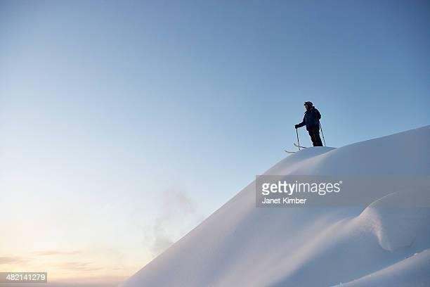 caucasian skier standing on snowy hilltop - スキー板 ストックフォトと画像