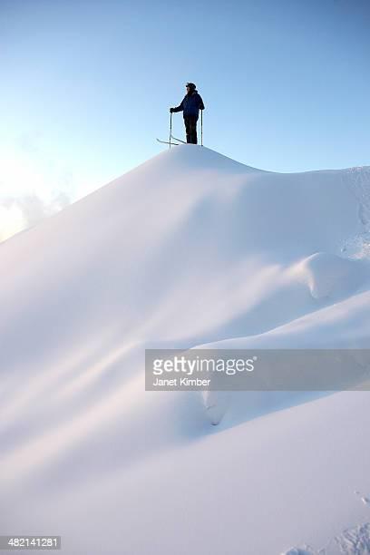 Caucasian skier standing on snowy hilltop