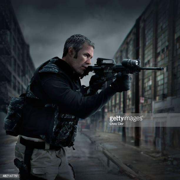 Caucasian sniper aiming gun on city street