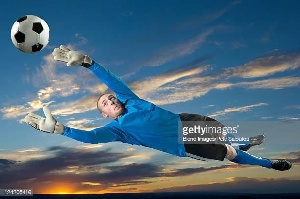 caucasian soccer goalie jumping in mid-air catching ball - torhüter stock-fotos und bilder