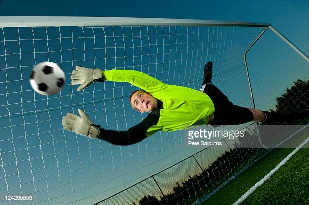 Caucasian soccer goalie jumping in mid-air catching ball