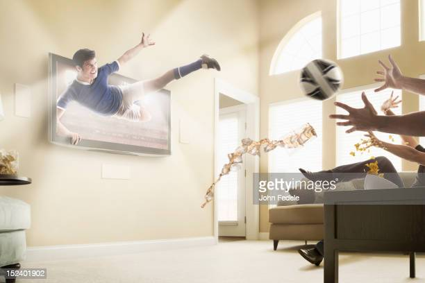 caucasian soccer player coming out of television set - watch what happens: live stock-fotos und bilder