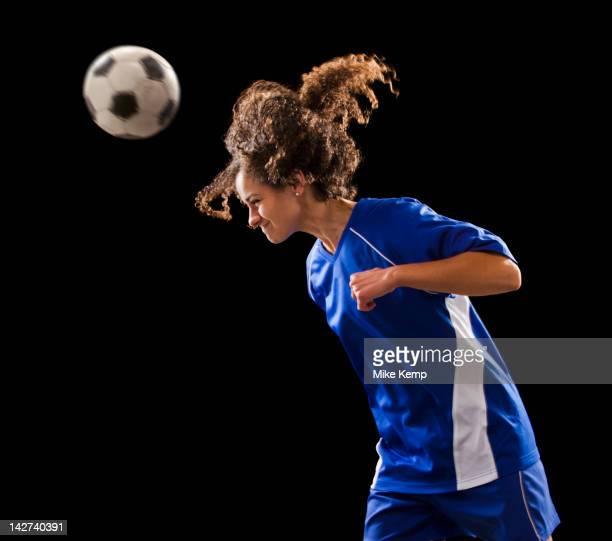 Caucasian soccer player heading the ball