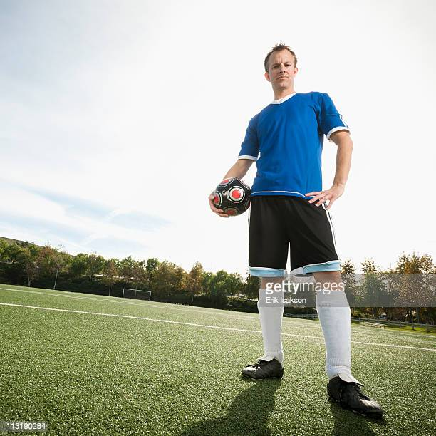 caucasian soccer player holding ball on soccer field - mid adult men stock pictures, royalty-free photos & images