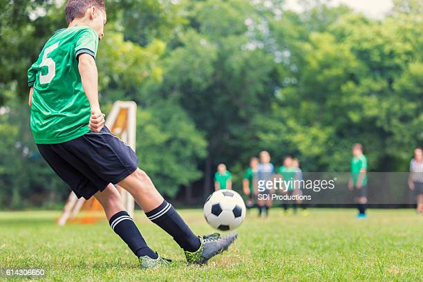 Caucasian soccer player kicks ball