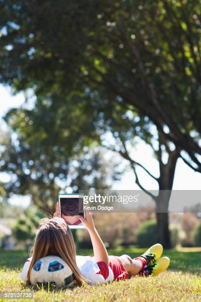 caucasian soccer player laying in grass using digital tablet - tenue de football photos et images de collection