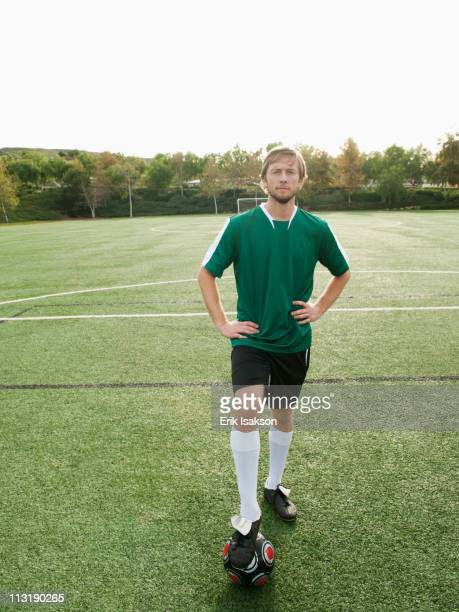 Caucasian soccer player standing on soccer field with ball