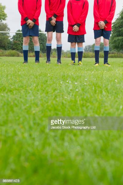 Caucasian soccer team forming wall and protecting groins