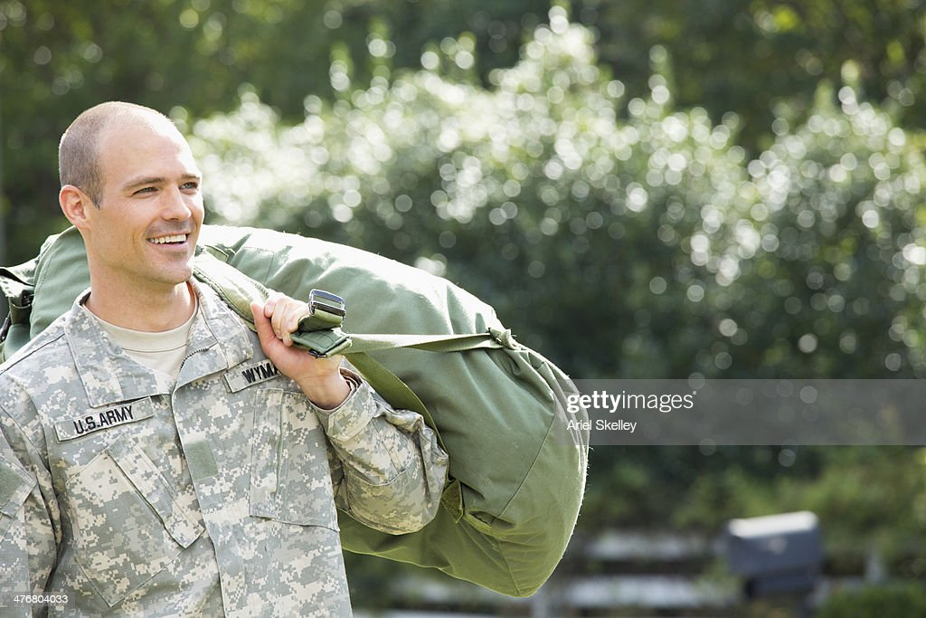 Caucasian soldier carrying duffel bag outdoors : Stock Photo