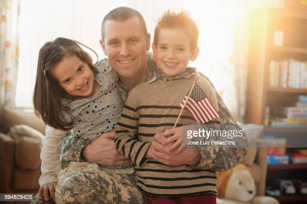 Caucasian soldier hugging children