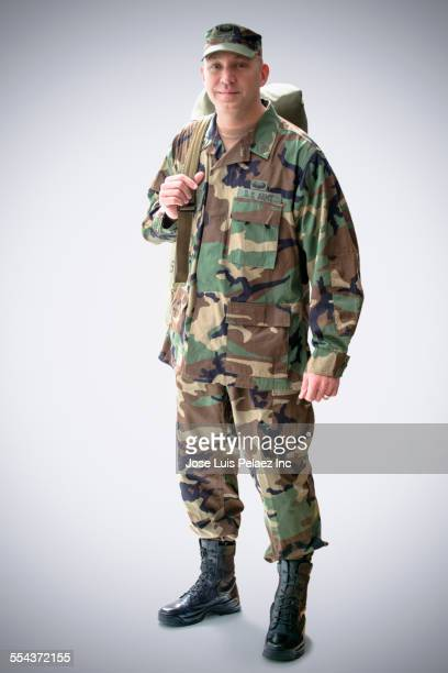 caucasian soldier in camouflage fatigues carrying sack - army soldier stock photos and pictures