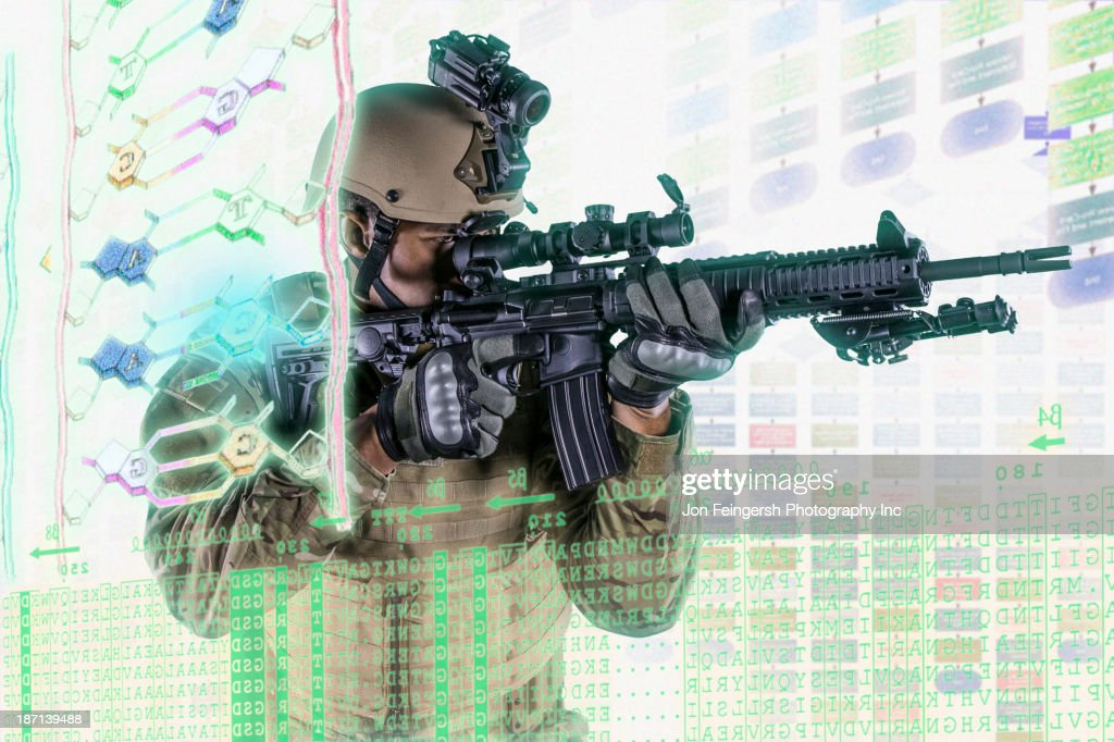 Caucasian soldier pointing gun at illuminated holograms : Stock Photo