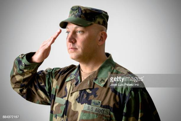 caucasian soldier saluting in camouflage fatigues - saluting stock pictures, royalty-free photos & images