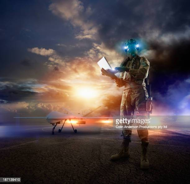 Caucasian soldier using laptop in combat zone