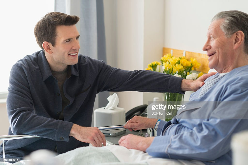 Caucasian son visiting father in hospital : Stock Photo