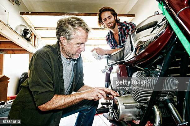 Caucasian son watching father repairing motorcycle in garage