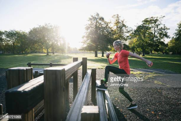 caucasian sportswoman in early 50s doing step-ups at park - clapham common stock pictures, royalty-free photos & images