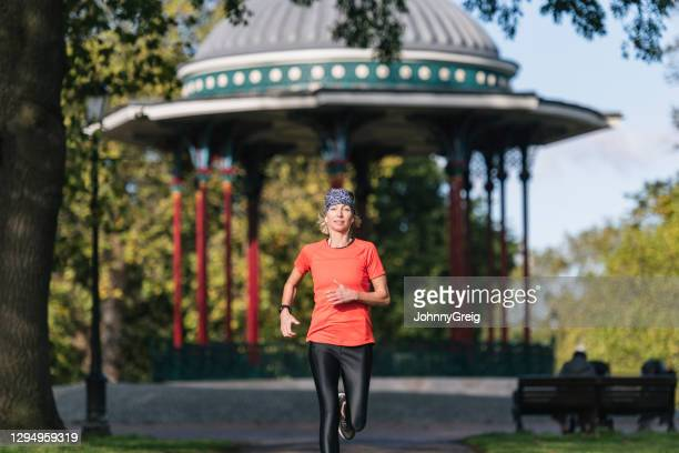 caucasian sportswoman in early 50s running at public park - clapham common stock pictures, royalty-free photos & images