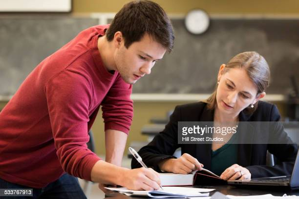 Caucasian student and teacher studying in classroom