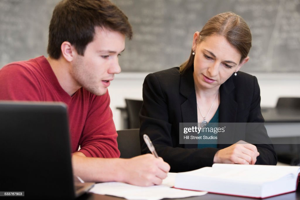 Caucasian student and teacher talking in classroom : Foto stock