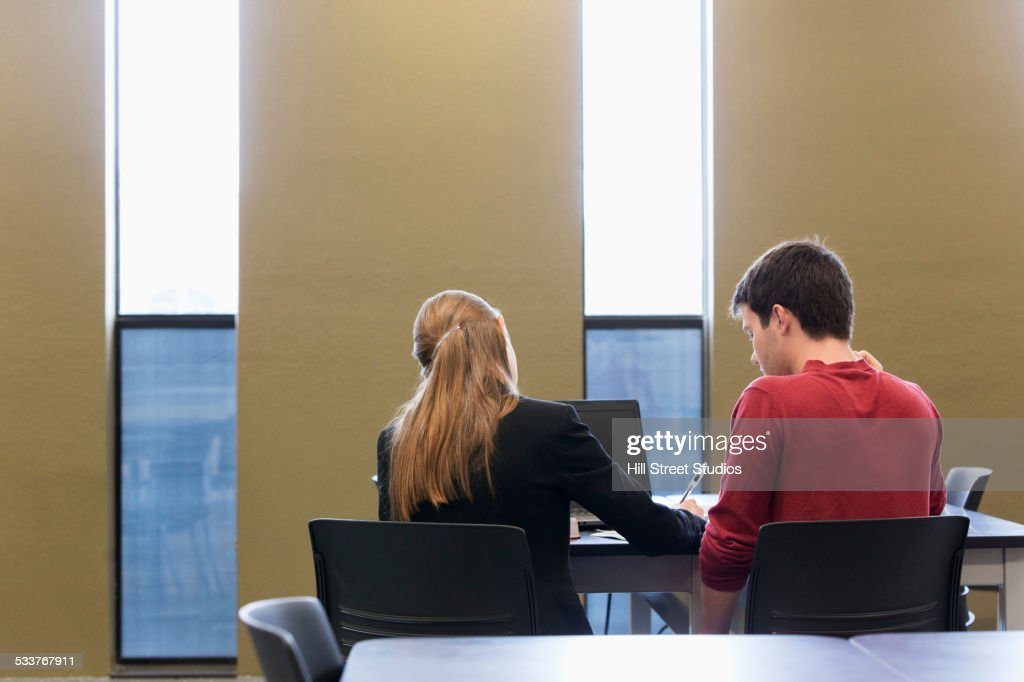 Caucasian student and teacher using laptop in classroom : Foto stock