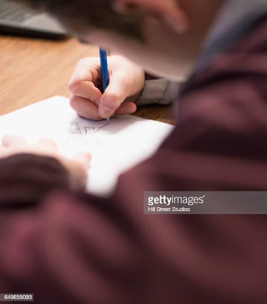Caucasian student doodling in classroom
