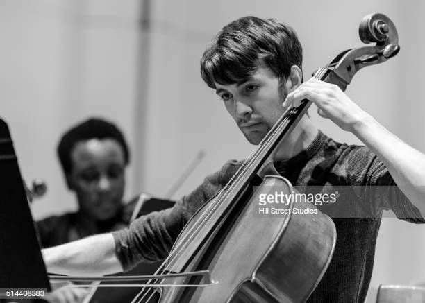 caucasian student playing cello in college orchestra - soloist stock photos and pictures
