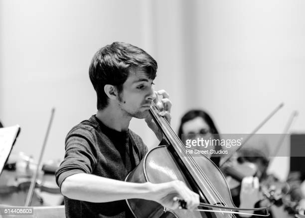Caucasian student playing cello in college orchestra