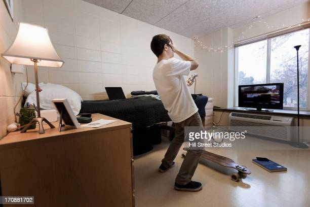 Caucasian student playing video games in dorm room