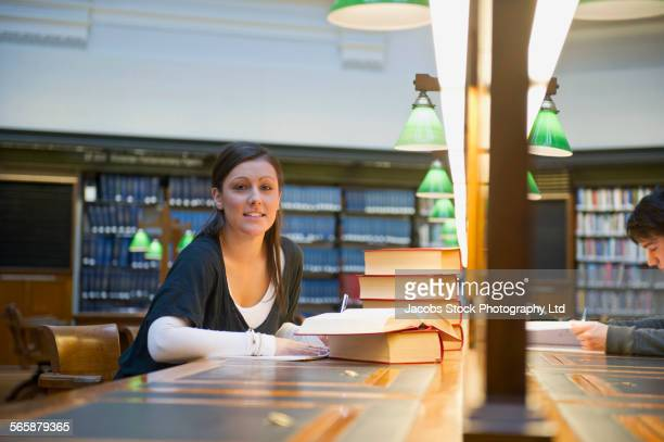 Caucasian student reading book in library