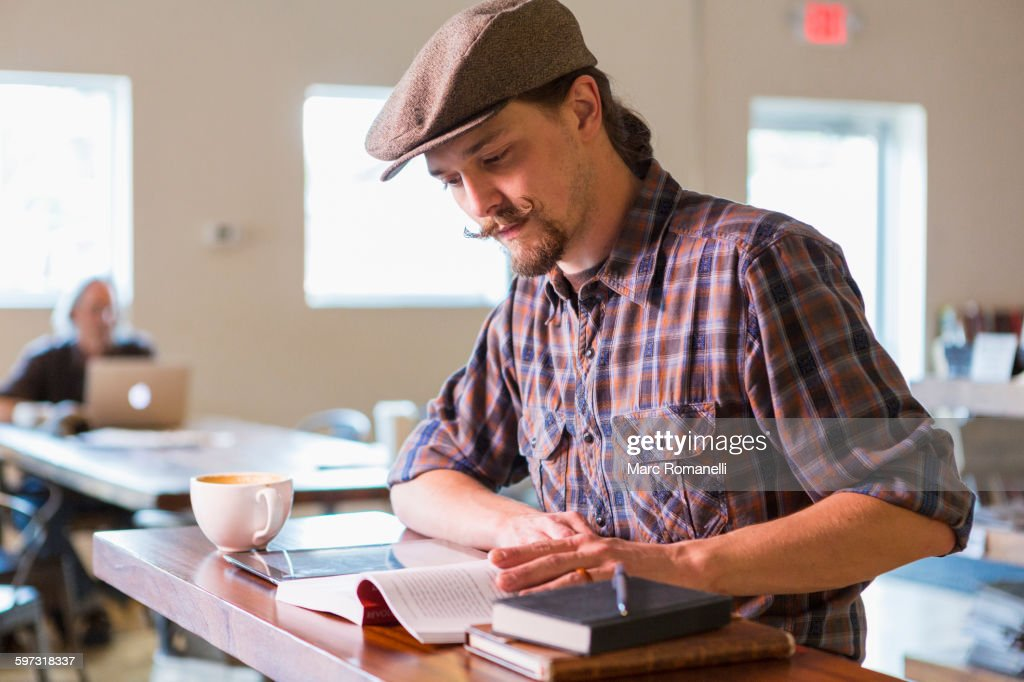 Caucasian student reading in cafe : Stock Photo
