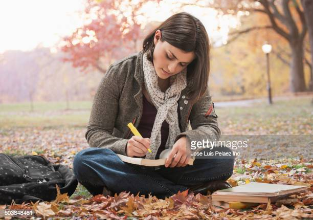 Caucasian student reading in park with autumn leaves