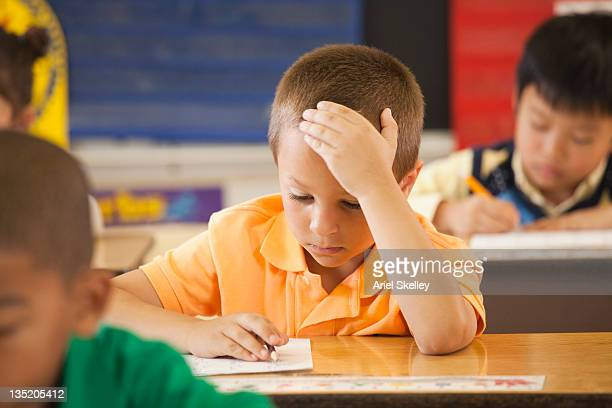 Caucasian student studying at desk in classroom