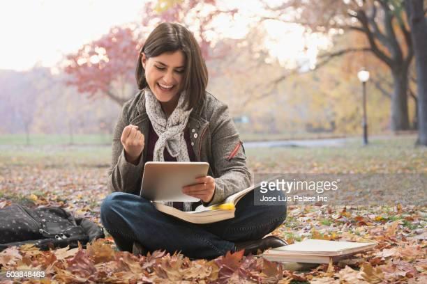 Caucasian student using digital tablet in urban park