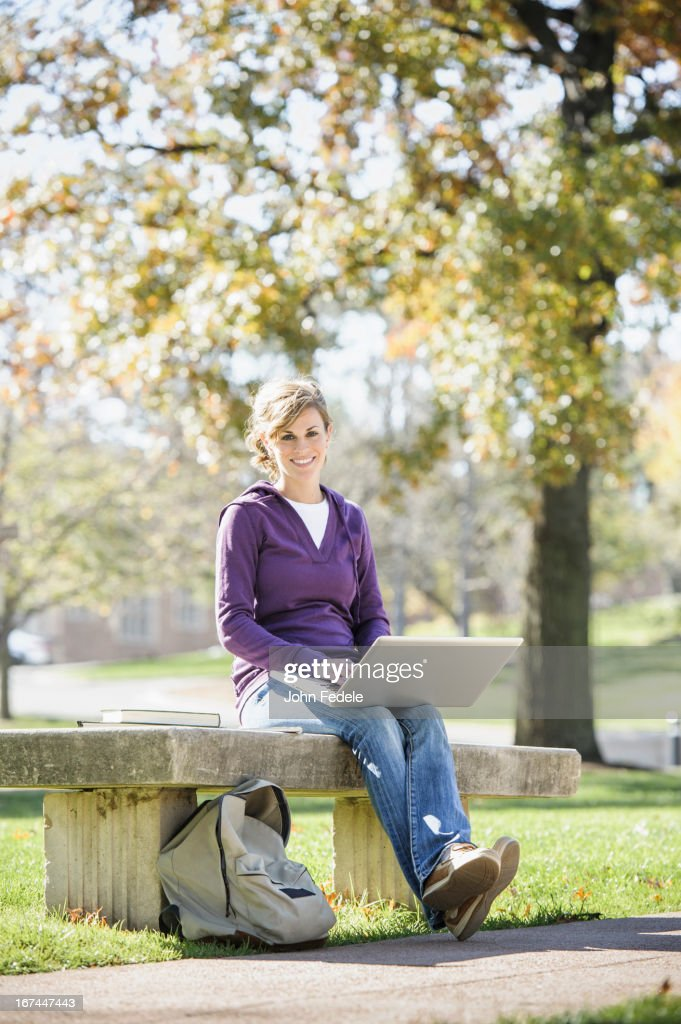 Caucasian student using laptop on campus : Stock Photo