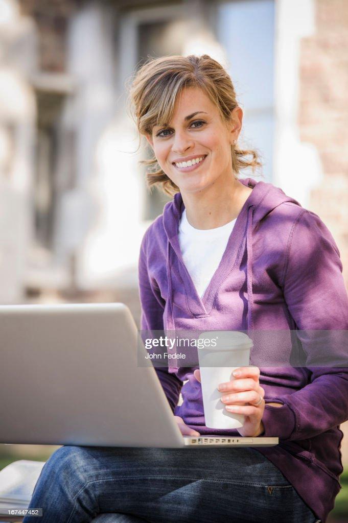Caucasian student using laptop on campus : Stock Photo