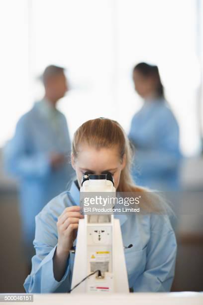 Caucasian student using microscope in lab