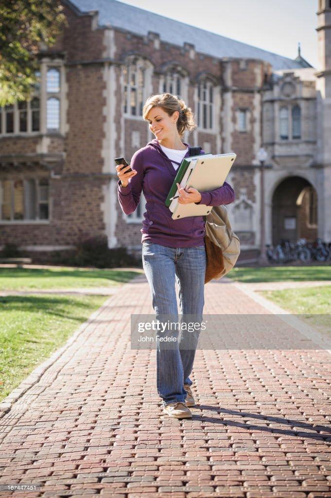 Caucasian student walking on campus : Stock Photo