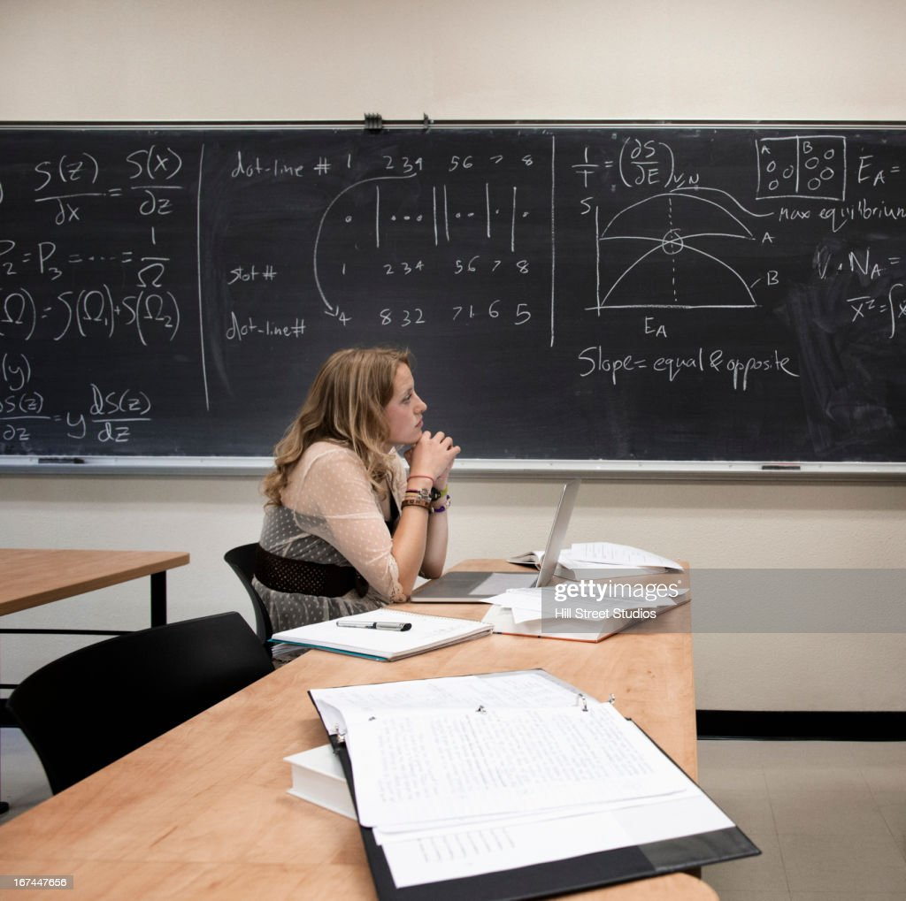 Caucasian student working in classroom : Stock Photo