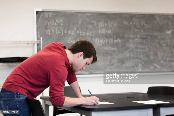 Caucasian student writing at table in classroom
