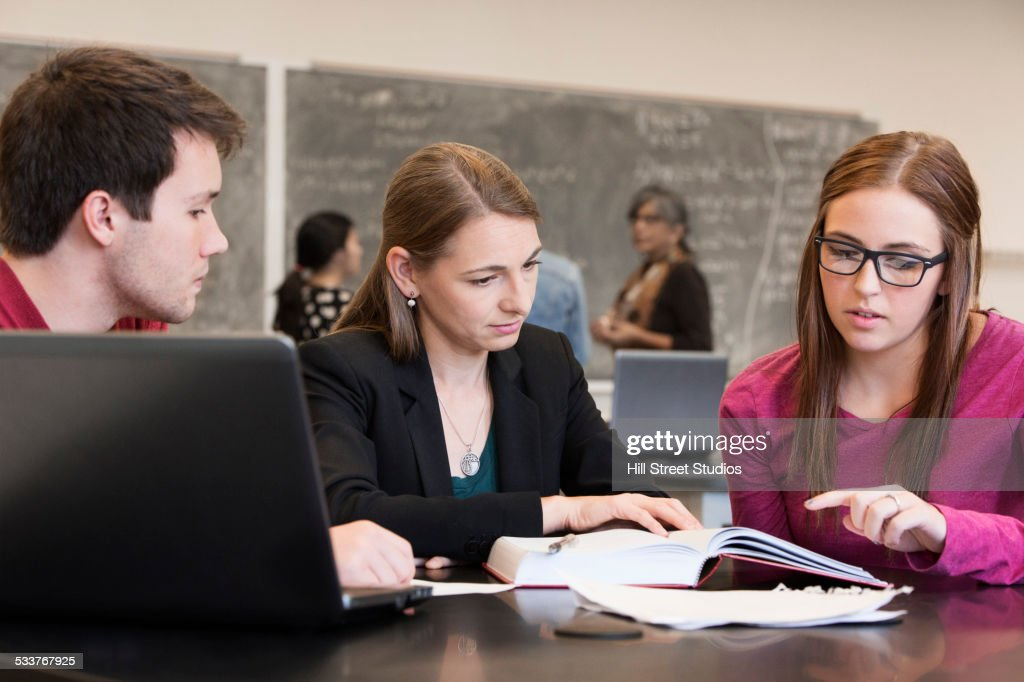 Caucasian students and teacher studying in classroom : Foto stock