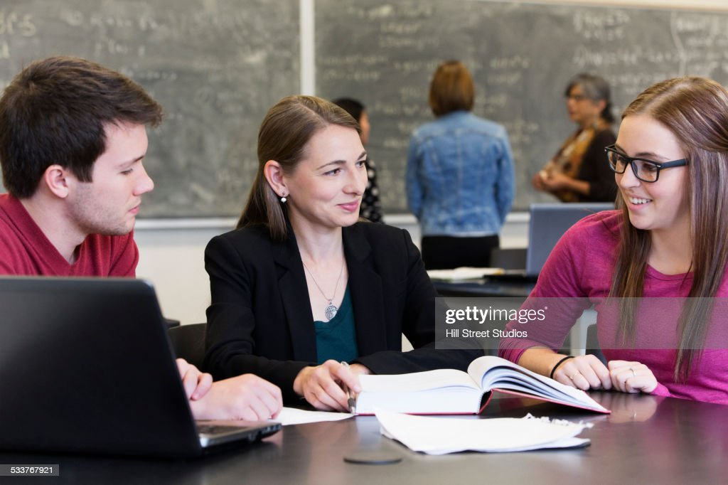 Caucasian students and teacher talking in classroom : Foto stock