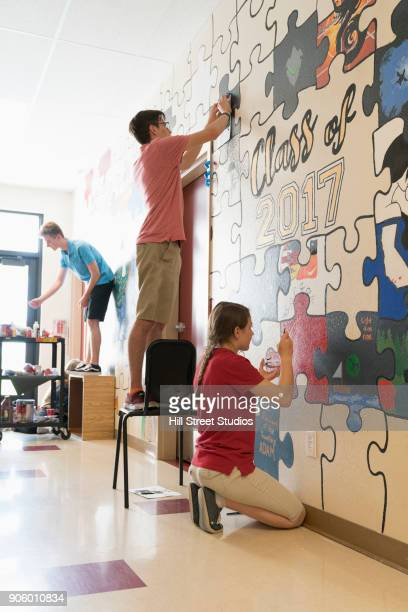 caucasian students painting mural on wall - pintar mural fotografías e imágenes de stock