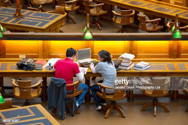 Caucasian students studying together in library