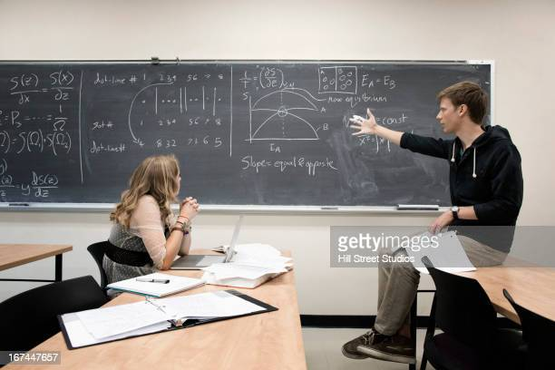 Caucasian students working in classroom