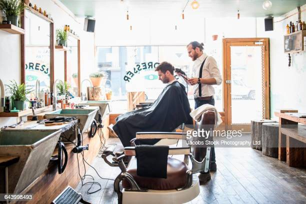 caucasian stylist cutting hair of customer in barber shop - hairstyle stock pictures, royalty-free photos & images