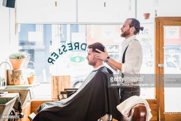 Caucasian stylist massaging scalp of customer in barber shop