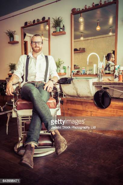 Caucasian stylist smiling in barber shop