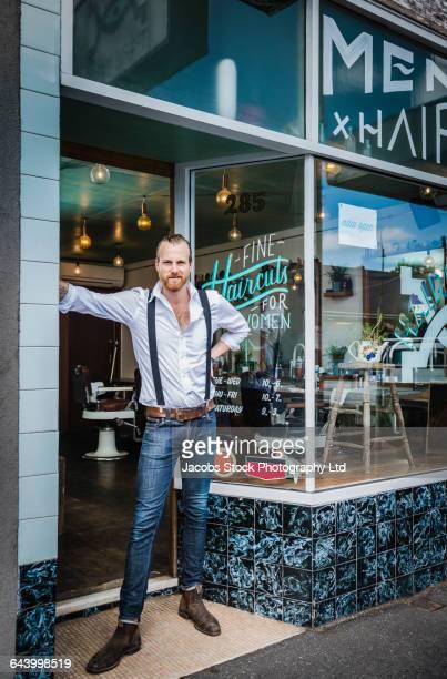 Caucasian stylist standing in barber shop doorway